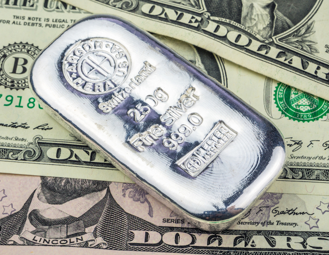 silver brick laying on dollar banknotes