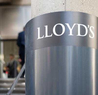 London, London/UK - April 10 2019: City worker in the background is seen leaving the Lloyds building. Sign for Lloyds is sharp, whereas city worker is blurred for effect.